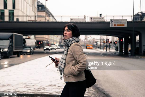 side view of young woman holding mobile phone while crossing road in city during winter - hands in pockets stock pictures, royalty-free photos & images
