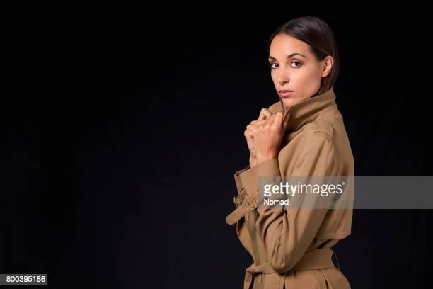 トレンチ コートを保持している若い女性の側面図