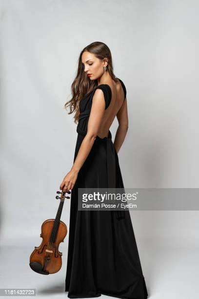 side view of young woman holding violin standing against white background - violin stock pictures, royalty-free photos & images
