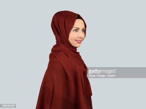Side View Of Young Woman In Hijab Standing Against Gray Wall
