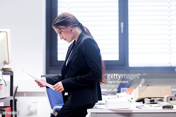 side view of young woman in office leaning against desk looking down at paperwork - sigrid gombert stock pictures, royalty-free photos & images