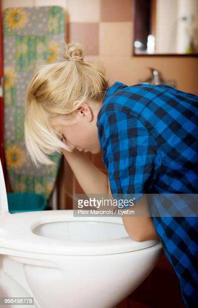 side view of young woman leaning on toilet bowl - vomiting stock photos and pictures