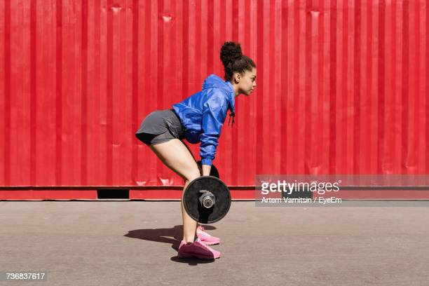 side view of young woman lifting barbell by red cargo container - barbell stock pictures, royalty-free photos & images