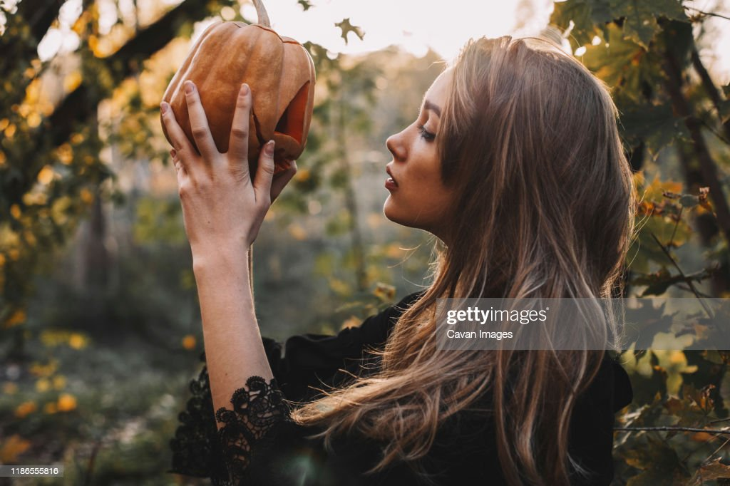 Side view of young woman looking at jack o' lantern in forest during Halloween : Stock Photo