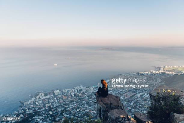 side view of young woman looking at view while sitting on mountain against sky during sunset - aussicht genießen stock-fotos und bilder