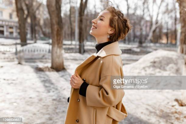 side view of young woman looking away in winter - overcoat stock pictures, royalty-free photos & images