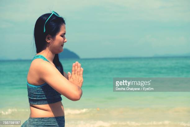Side View Of Young Woman Meditating While Standing At Beach Against Sky