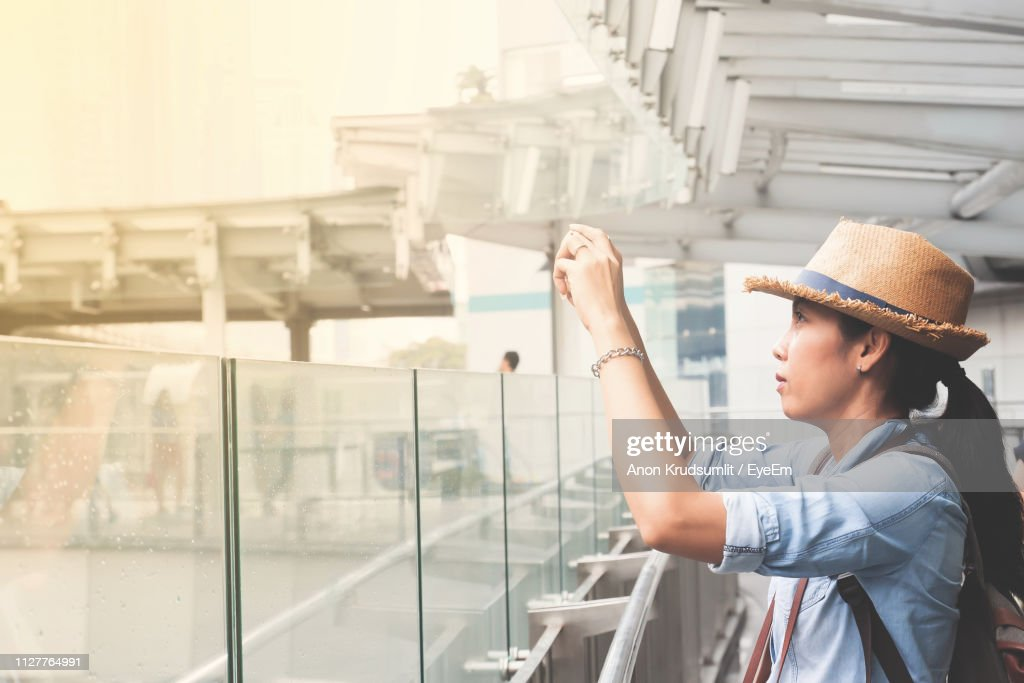 Side View Of Young Woman Photographing While Standing Against Railing : Foto de stock