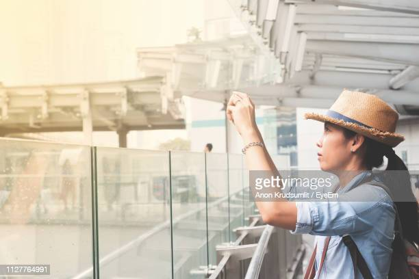 Side View Of Young Woman Photographing While Standing Against Railing