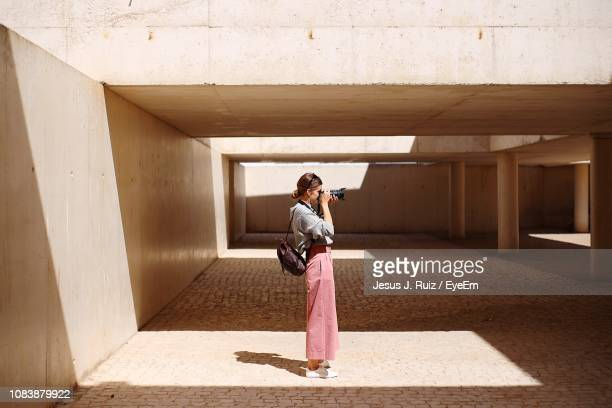 side view of young woman photographing while standing in building - 僅一名年輕女人 個照片及圖片檔