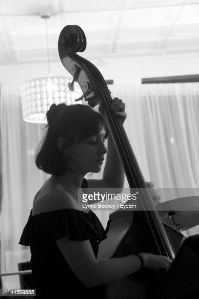 side view of young woman playing double bass - violin family stock photos and pictures