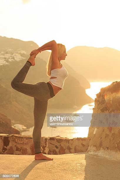 Side view of young woman practicing at sunset in Santorini