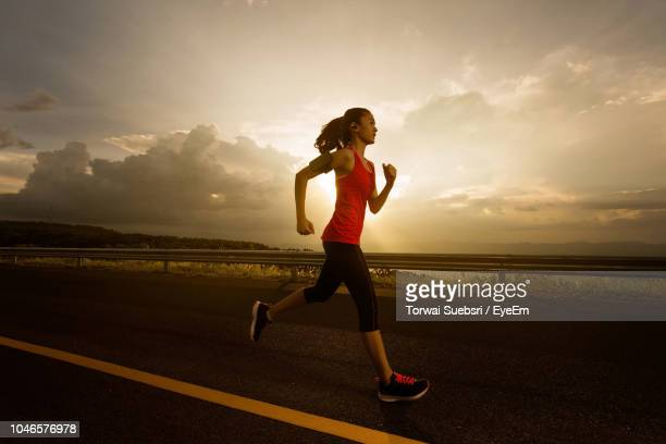 side view of young woman running on road against cloudy sky during sunset - torwai stock pictures, royalty-free photos & images