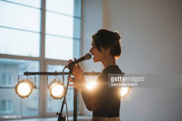side view of young woman singing indoors - singing stock pictures, royalty-free photos & images