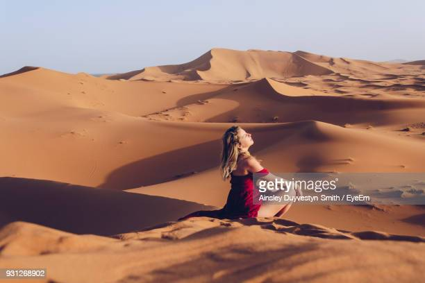Side View Of Young Woman Sitting At Desert
