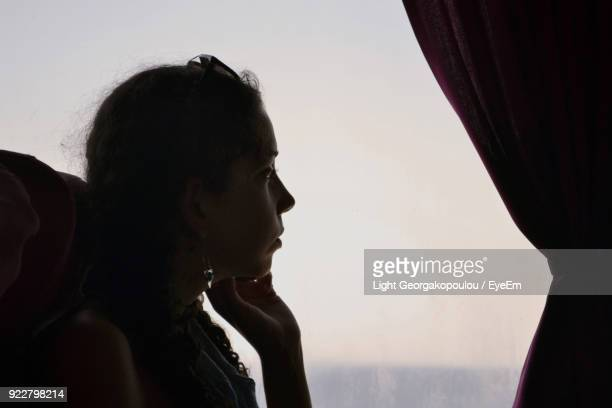 Side View Of Young Woman Sitting By Window In Bus