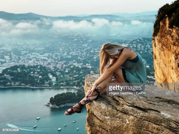 Side View Of Young Woman Sitting On Mountain By Sea Against Sky