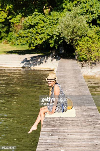 Side view of young woman sitting on wood pier wearing panama hat looking away, Schondorf, Ammersee, Bavaria, Germany