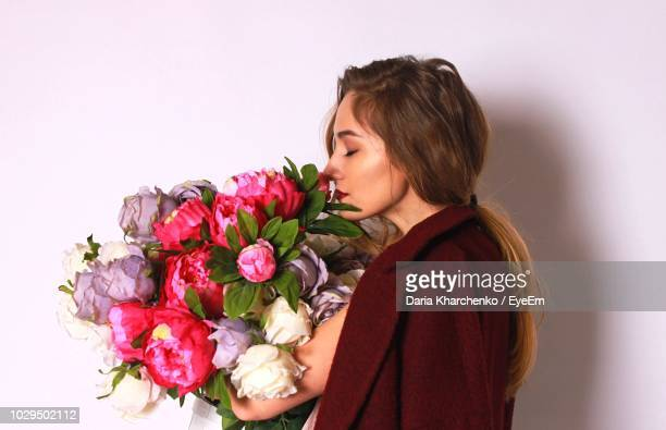 side view of young woman smelling bouquet against white background - multi colored coat stock photos and pictures