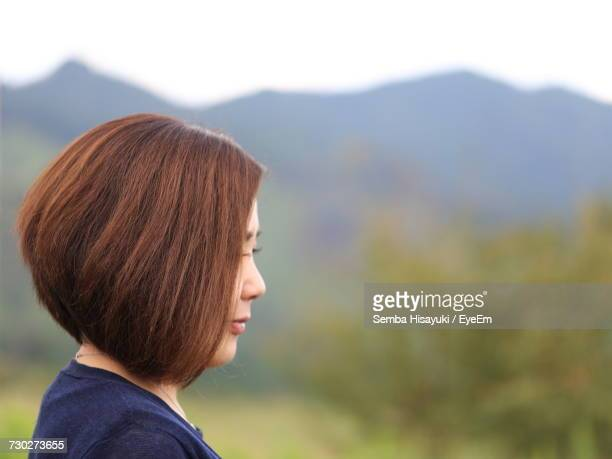 Side View Of Young Woman Standing Against Mountains
