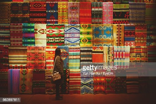 Side View Of Young Woman Standing Against Multi Colored Carpets On Display For Sale