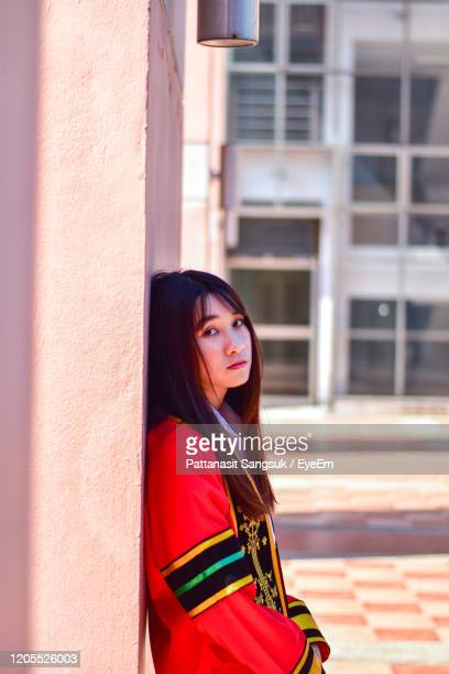 side view of young woman standing against wall against building - pattanasit stock pictures, royalty-free photos & images