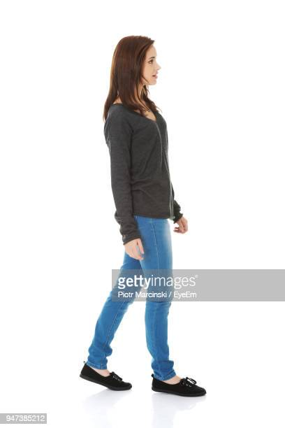 side view of young woman standing against white background - van de zijkant stockfoto's en -beelden