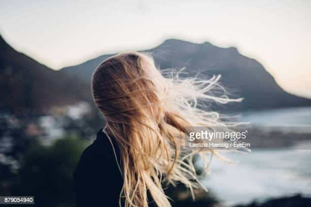 side view of young woman standing at beach against clear sky during sunset - wind stockfoto's en -beelden