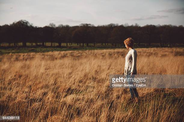 side view of young woman standing on field at richmond park - bortes cristian stock photos and pictures