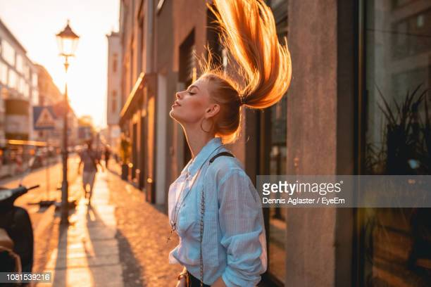 side view of young woman standing on street - city life stock-fotos und bilder