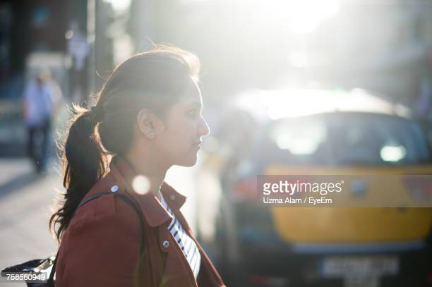 Side View Of Young Woman Standing Outdoors On Sunny Day