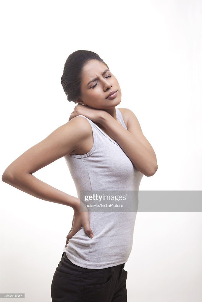 Side view of young woman suffering from back and shoulder ache over white background : Stock Photo