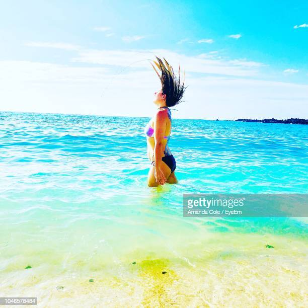 Side View Of Young Woman Tossing Wet Hair In Sea Against Sky During Sunny Day