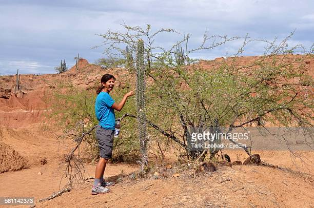 Side View Of Young Woman Touching Cactus
