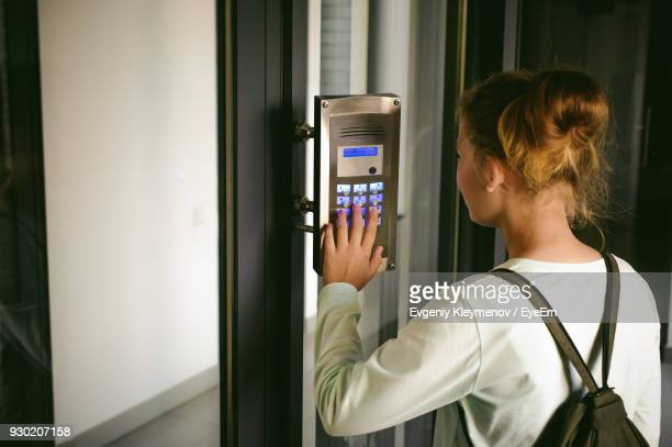 side view of young woman using intercom - intercom stock photos and pictures