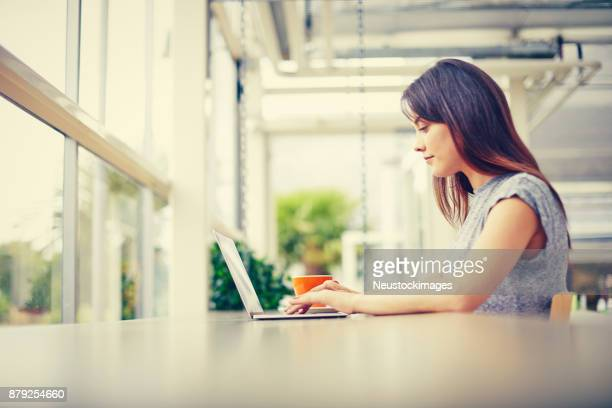Side view of young woman using laptop at cafe table