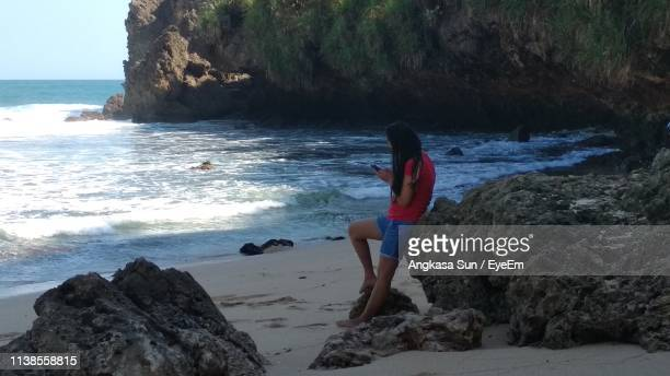 Side View Of Young Woman Using Mobile Phone While Standing By Rock At Beach