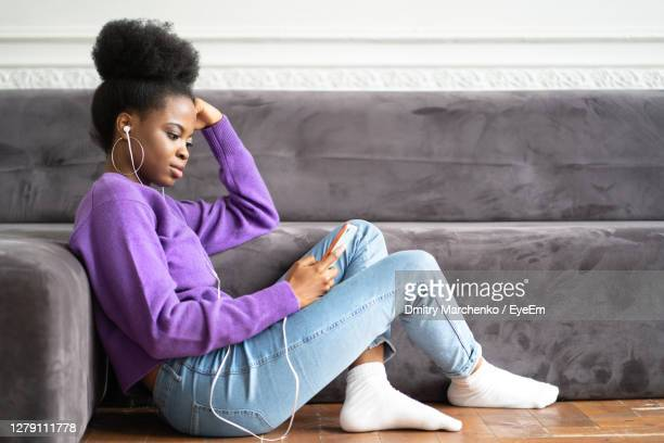 side view of young woman using smart phone siting on floor - black jeans foto e immagini stock