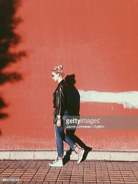 side view of young woman walking on footpath against wall - blouson en cuir photos et images de collection