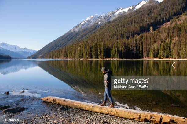 side view of young woman walking on log at lakeshore against mountain - whistler british columbia stock pictures, royalty-free photos & images