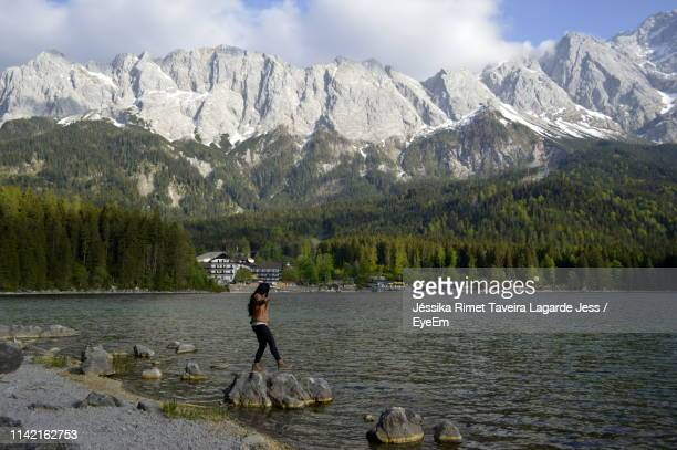 side view of young woman walking on rocks in lake against mountains - lagarde stock pictures, royalty-free photos & images