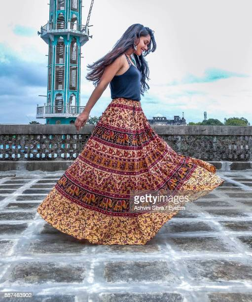 side view of young woman wearing skirt while walking on footpath - ankle length stock pictures, royalty-free photos & images