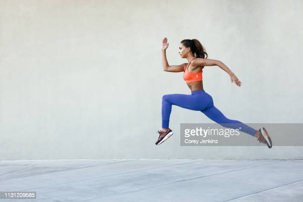 side view of young woman wearing sports clothing in mid air striding stance - striding stock pictures, royalty-free photos & images