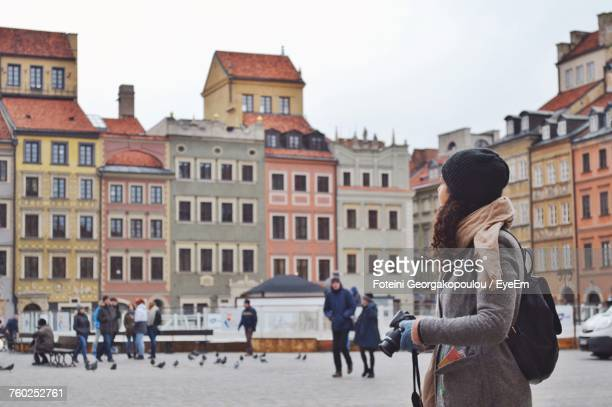 Side View Of Young Woman Wearing Warm Clothing With Camera Standing On City Street
