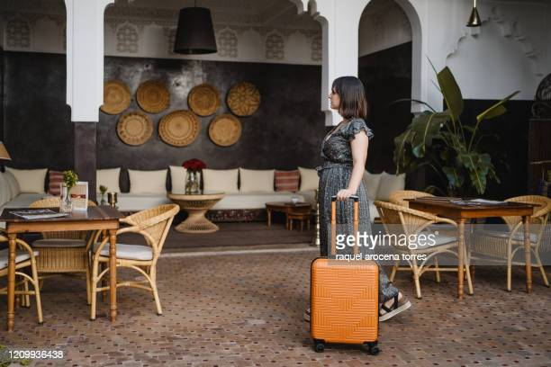 side view of young woman with an orange suitcase in the hotel - orange dress stock pictures, royalty-free photos & images