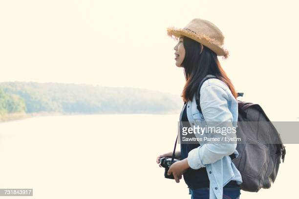 Side View Of Young Woman With Camera Standing By Lake Against Clear Sky