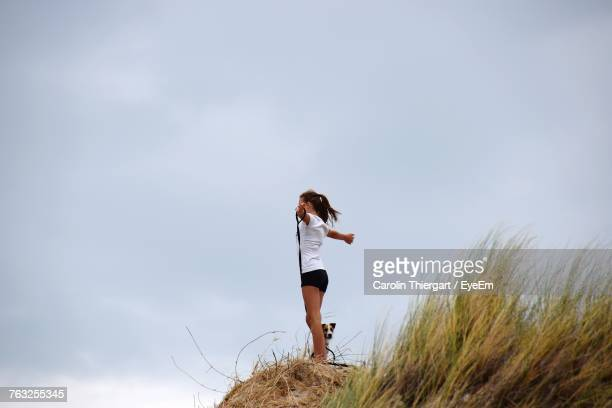 Side View Of Young Woman With Dog Standing On Rock At Beach Against Sky