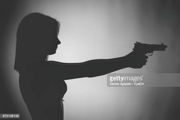 side view of young woman with gun against white background - gun stock pictures, royalty-free photos & images