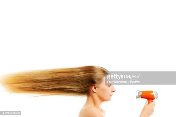 Side View Of Young Woman With Long Hair Holding Hair Dryer Against White Background