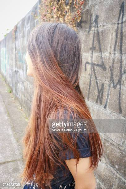 side view of young woman with long hair standing by wall - highlights hair stock pictures, royalty-free photos & images